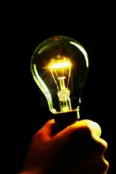 12645050-hand-holding-a-lit-lightbulb-in-a-dark-place